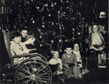 Children, three in wheelchairs, around a decorated Christmas tree.