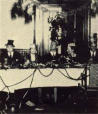 Three man and two women in strange hats sit at a table.