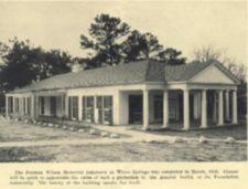 Photograph of the infirmary, a single-story building with pillars.