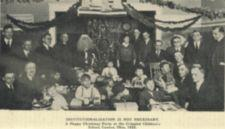 A group of children with presents, surrounded by adults, one dressed as Santa Claus.