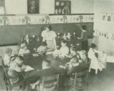 A teacher supervises a classroom with eleven children.