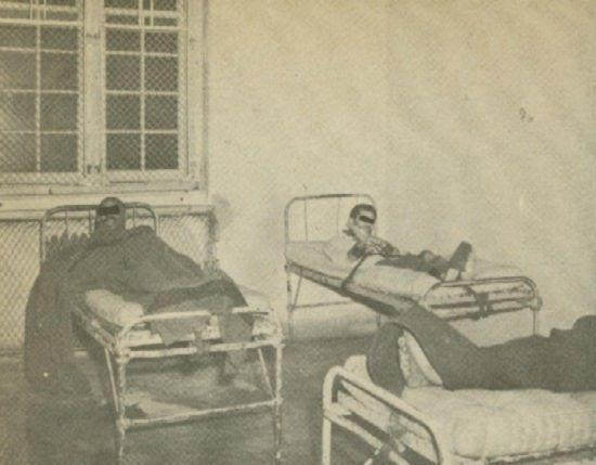 An Image of two beds. In each bed is a male presenting person who has straps holding them down across the waist with further restraints binding the feet together and to the bed, as well as the hands.
