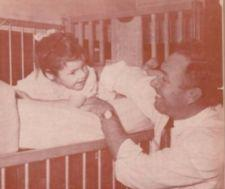 A smiling father plays with a young girl in a crib.