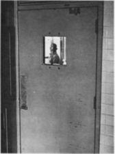 A man seen through the barred window of a door.