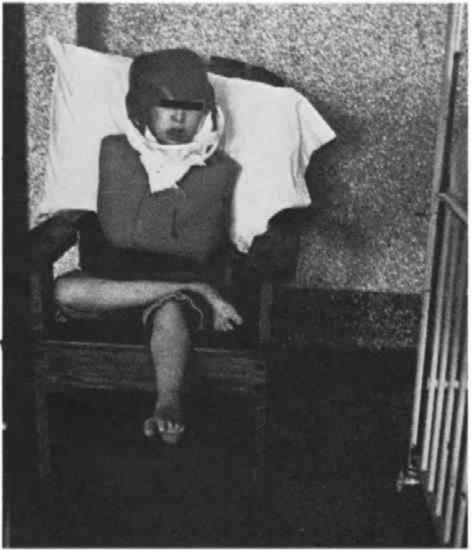 A Young person with dark hair is tied to a wooden chair, a restraining jacket additionally used to restrain them.