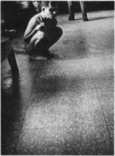 A naked young man crouching on a stone floor.