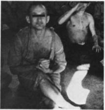 Two partially dressed men sitting on a floor,