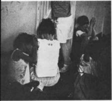 Children sitting on a floor in a dilapidated room.
