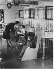 A woman feeding a child in a high chair. The decorated room has cribs.