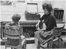 "A boy, in a chair marked ""Fred,"" sits next to a woman and a record player."