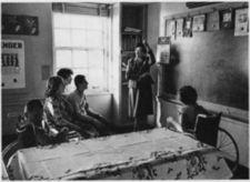 A teacher with four children in a classroom.