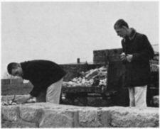 Two young men with rocks gathered in a cart next to a stone wall.