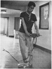 A man using a floor buffer in a hall.