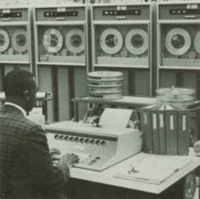 An African American man works at an early computer.