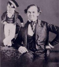 P.T Barnum sits in a chair.  Tom Thumb, with hand on Barnum's shoulder and in uniform, stands on table.