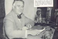 FDR sits at desk with CBS and NBC radio microphones.