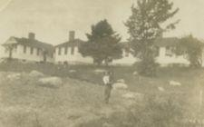 A man holds a boy in a rocky field before several small white buildings.