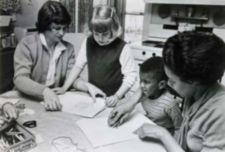 Two adults showing two children how to color.