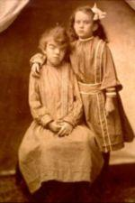 One sister sits on a stool with her hands folded in her lap. The other stands with her arm around her sister.