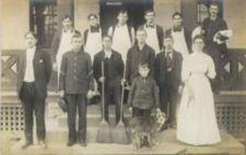 Photograph of men, one woman, one child, and a dog posing on the porch of a building.