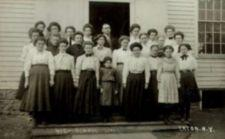 Photograph of girls and male teacher on front steps of school building.  One of the girls is short-statured.