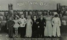 Photograph of eight short-statured people standing in line, arms interlocked, dressed in formal wear.