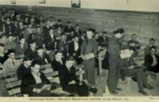 A group of civilian men sit on benches as two men in military uniforms hand out exams