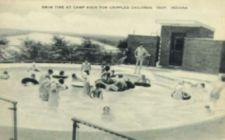 Postcard photograph of children playing in a pool.