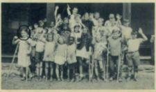 "Group photograph of campers waving.  One girl is circled in pen and labelled ""Me."""