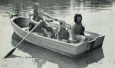 Photograph of young man helping a boy row a rowboat.  Two girls are also in the boat.