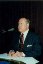 Jernigan at a sitting at a table in front of a microphone.