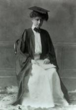Helen Keller sits in a straightback wooden chair wearing cap and gown.