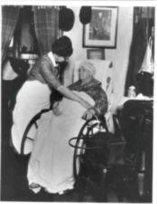 Elderly woman in wheelchair, with blanket over her legs, is tended by nurse.