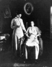 Woman in wheelchair having her pulse taken by nurse