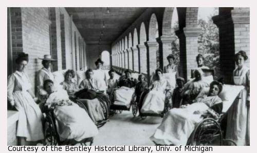 Seven women sit in large wheelchairs on the porch of a large Victorian house at a sanitarium. Each is covered in a blanket and looks passively at the camera. Six attendants and two children stand behind and amongst them.