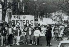 "A crowd of protesters marches down a street.  A man holds a banner that reads ""The Board Busters."""