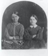 Two women pose with their arms crossed against their chests