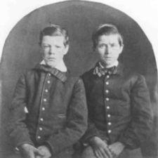 Photograph of two young boys with buttoned coats and bow ties.
