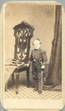 A short-statured young man in a military uniform stands next to a chair.