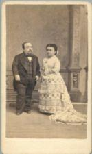 A short-statured man and woman dressed formally.