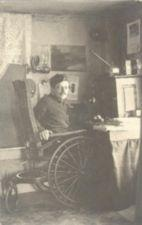 A man in a wooden wheelchair looks up from his desk.