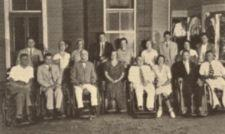 A group of seventeen people, some in wheelchairs, some standing.