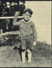 A boy holds up one arm.