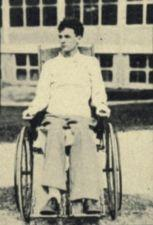A young man sits in a wheelchair.
