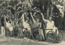 Five women in a row of wheelchairs, the last pushed by a young man.