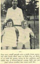 Two children sit in a swing with a nurse standing behind them.