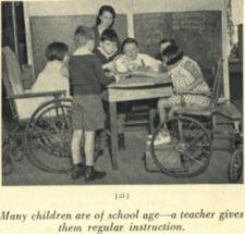 Six children, two in wheelchairs, examine a globe, their teacher in the background.