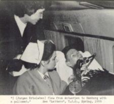 A man with a respirator attended by a nurse on a plane.