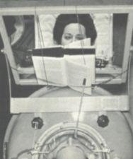 A woman in an iron lung reads a book using a mouthstick.