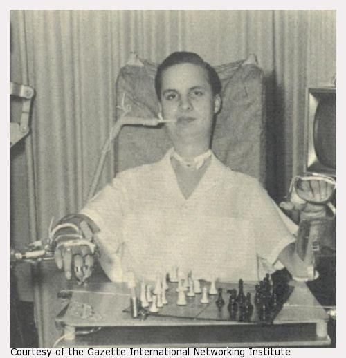 A young man plays chess with assitive technology.
